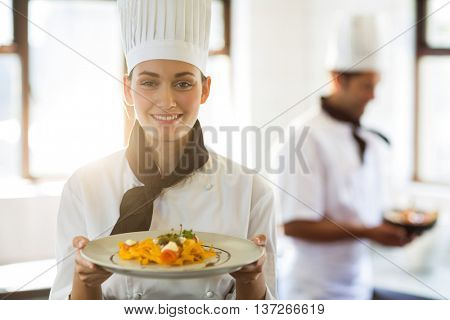 Happy head chef presenting her food in the commercial kitchen while chef working behind her