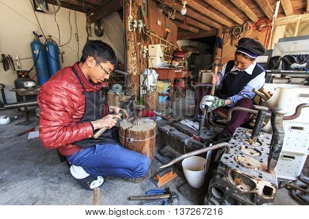 Heqing: China - March 16 2016: Young silversmith working on his workshop along with another woman dressed with the traditional Bai attire.