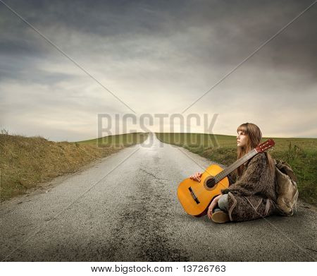 Young woman with guitar and backpack sitting on a countryside road