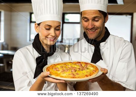 Two head chef presenting a pizza in commercial kitchen
