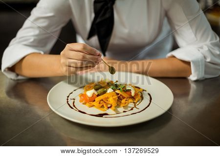 Mid section of chef garnishing pasta dish with olive in commercial kitchen