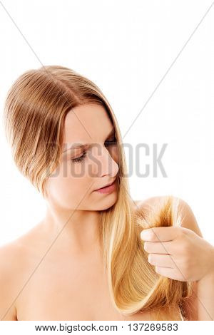 Shocked woman showing her damaged split ends of hair.