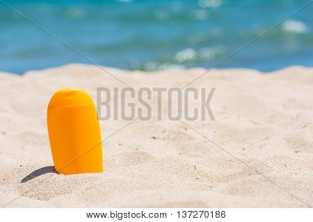 Sunscreen bottle on the beach. Close up