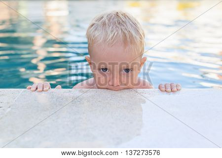 Child learn to swim - funny face portrait of little baby boy in pool. Active healthy lifestyle water sport physical activity and swimming lessons with parents on summer family holiday with child.