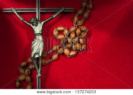Close up of metal crucifix with Jesus and wooden rosary beads. On a red velvet background
