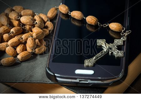 Macro photo of a metal crucifix with wooden rosary beads on a used smartphone and Holy Bible