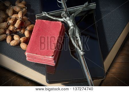 Close up of a silver crucifix with wooden rosary beads on a smart phone and two Holy Bibles