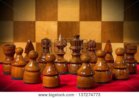 Macro photography of the wooden chess pieces on a red velvet with wooden chess board on the background