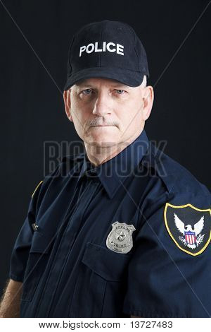 Portrait of a serious police officer, photographed over a black background.