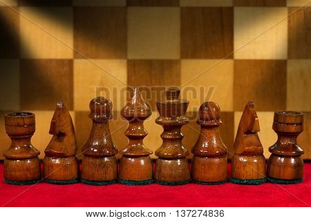 Macro photography of some wooden chess pieces on a red velvet with wooden chess board on the background