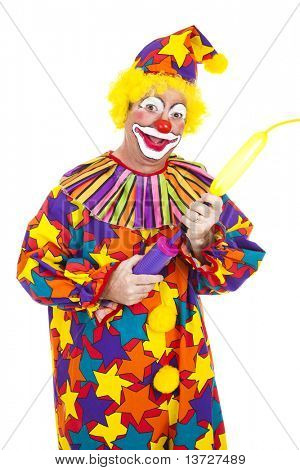 Funny birthday clown blows up a balloon to twist into an animal shape.  Isolated.
