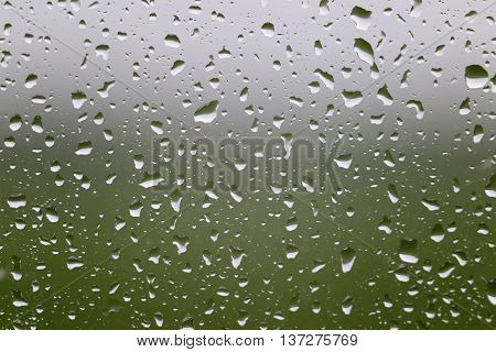 Rainy weather. Water raindrop on window glass with green meadow and gray sky