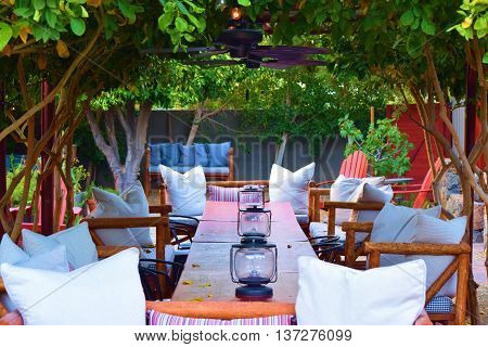 Intimate comfortable outdoor table and chairs with rustic style lamps surrounded with plants taken in a residential garden