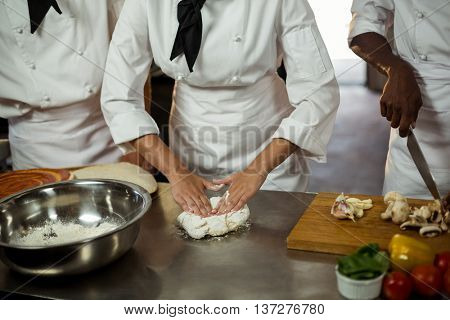 Mid section of head chef making pizza dough in commercial kitchen