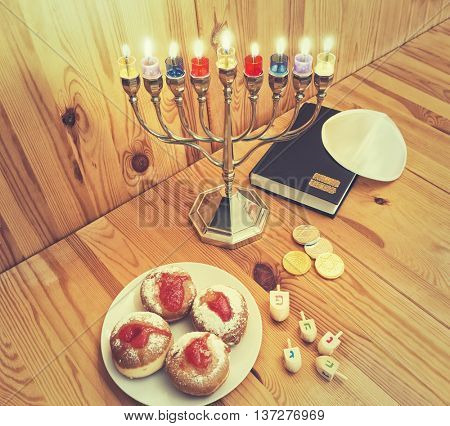 Jewish Holiday Hanukkah With Silver Menorah (traditional candelabra) with Burning candles, Torah, Donuts And Wooden Dreidels,