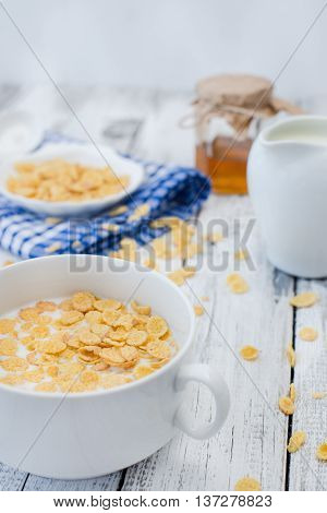 Cornflakes and milk on white wooden background. Morning breakfast. Rustic style.