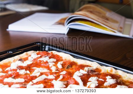A raw pizza with mozzarella cheese tomatoes and tuna ready to be put into the oven with recipe book in the background