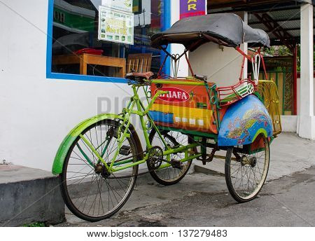 JOGJAKARTA INDONESIA- JAN 16: Becak are waiting for clients in the street on jan 16 2011 in Jogjakarta Indonesia. Riding a cycle rickshaw a popular form of taxi here.