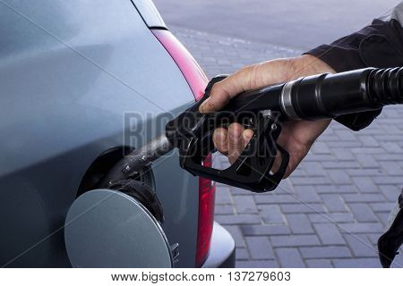 car fill with gasoline at a gas station.