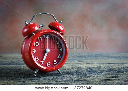 Red double bell alarm clock and book on wooden background