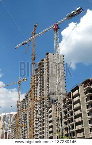 New high-rise modern apartment buildings construction in process ob bright sunny day side view vertical
