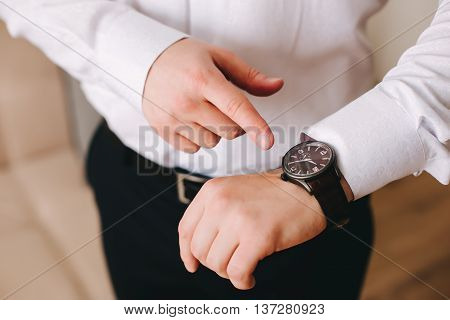 businessman in white shirt looking at his wristwatch on his hand and watching the time