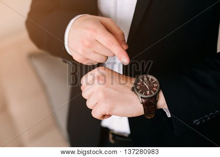 businessman in black suit look at his expensive swiss wristwatch on his hand and watching the time