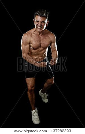bodybuilder sport man with big strong body pressing and showing his muscles in angry furious and concentrated face isolated on black background in fitness and bodybuilding workout