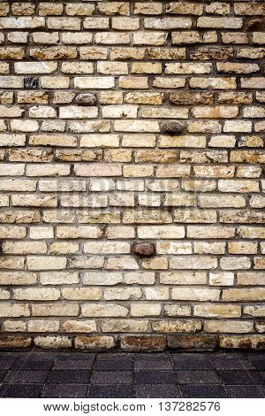 Yellow brick wall with some stones in it abstract architecture background