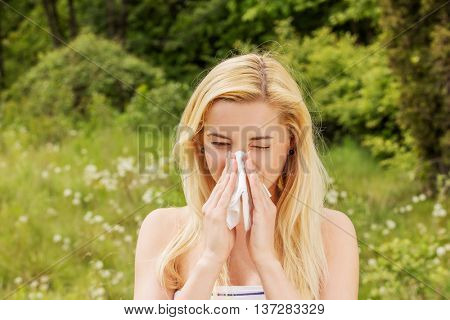 Girl with alergy blowing her nose.