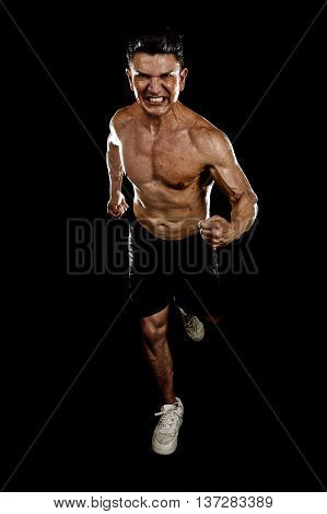strong and fit man with ripped body muscles running determined and hard doing sprint workout with naked torso isolated on black background in sport condition and training concept