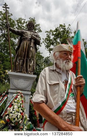 SOFIA BULGARIA - JUNE 8: Bulgarian military veteran holds the national flag in front of newly opened monument of the Bulgarian Tsar Samuil (997-1014) on June 8 2015 in Sofia.