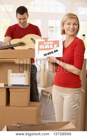 Happy woman holding sold sign in new house, smiling man unpacking boxes in background.?