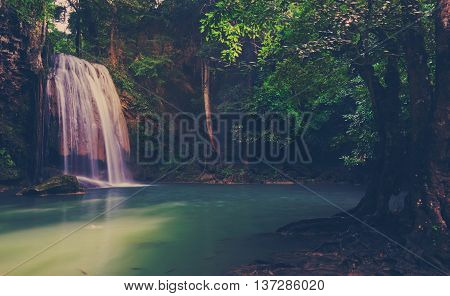 Tropical rainforest waterfall in Kanchaburi Thailand. Vintage filtered effect image