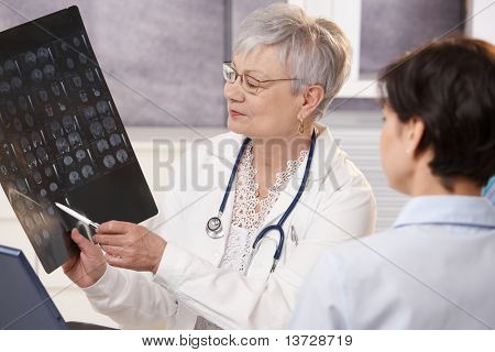 Doctor and patient discussing x-ray results in doctor's office.?