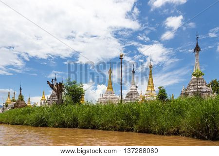 gold and white Buddhist stupa in the grass on the shore of Inle Lake with blue sky and clouds
