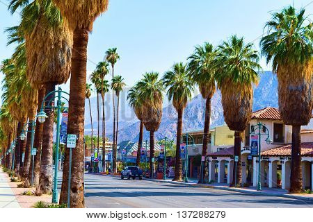 June 28, 2016 in Palm Springs, CA:  Palm Tree lined Palm Canyon Drive which is the main street thru Downtown Palm Springs surrounded with retail stores and restaurants for tourists and locals to enjoy, entertainment, shopping, and dining taken in Downtown