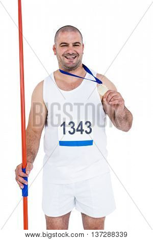 Athlete with game gold medal holding javelin on white background