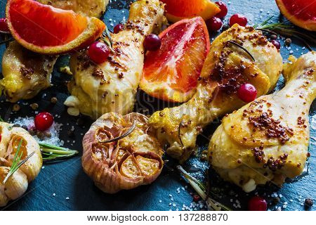 Roasted chicken legs red oranges cranberries garlic and rosemary on the black background. Cooked with sauce from mustard orange honey and olive oil