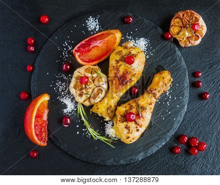 Roasted chicken legs red oranges cranberries garlic and rosemary on the black background. Cooked with sauce from mustard orange honey and olive oil. Top view.