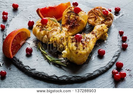 Roasted chicken legs red oranges cranberries garlic and rosemary on the black background. Cooked with sauce from mustard orange honey and olive oil.
