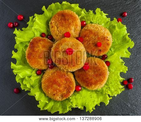Roasted chicken cutlets on green lettuce. Dark stone background. Top view.