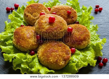 Roasted chicken cutlets on green lettuce. Dark stone background.