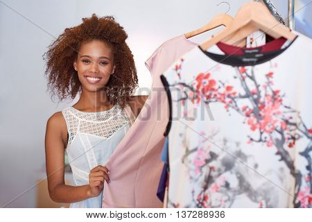 Portrait of an attractive young woman browsing through clothes hanging on racks while standing in a clothing store