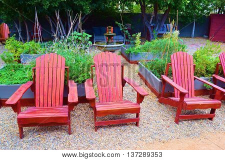Residential garden with rustic wooden chairs, water fountain, and plants