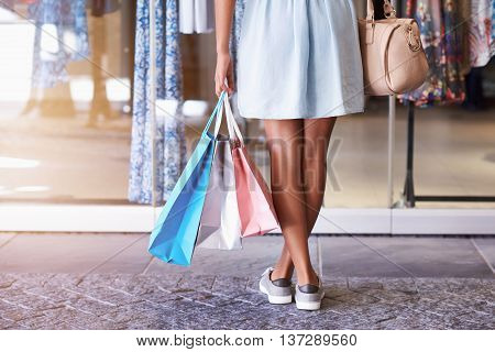Closeup of a young woman's legs standing in front of a clothing store holding many shoppping bags and her handbag, standing in front of a store window