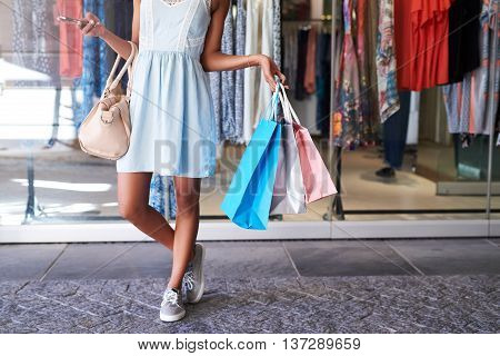 Closeup of a young woman's legs standing in front of a clothing store holding many shoppping bags and her cellphone, standing in front of a store window