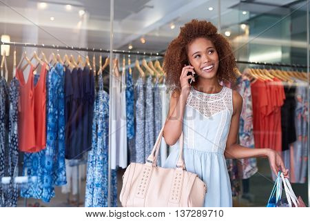 Attractive young woman with curly hair talking on her cellphone and carrying shopping bags while enjoying a day at the mall