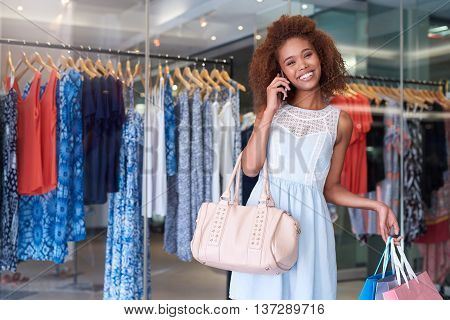 Portrait of an attractive young woman with curly hair talking on her cellphone and carrying shopping bags while enjoying a day at the mall