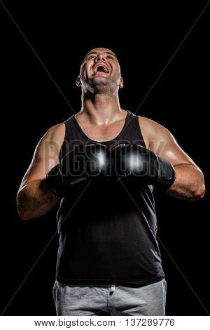 Boxer in boxing gloves laughing on black background